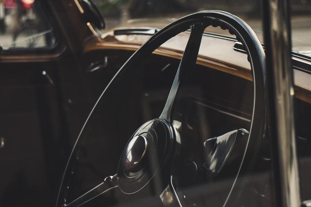 black steering wheel in selective focus photography