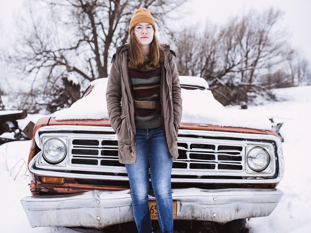 woman leaning on snow covered car