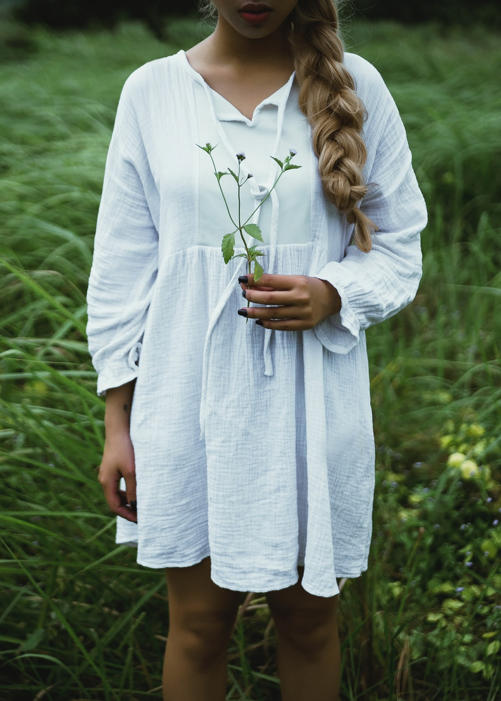 woman in white long-sleeved dress on gras