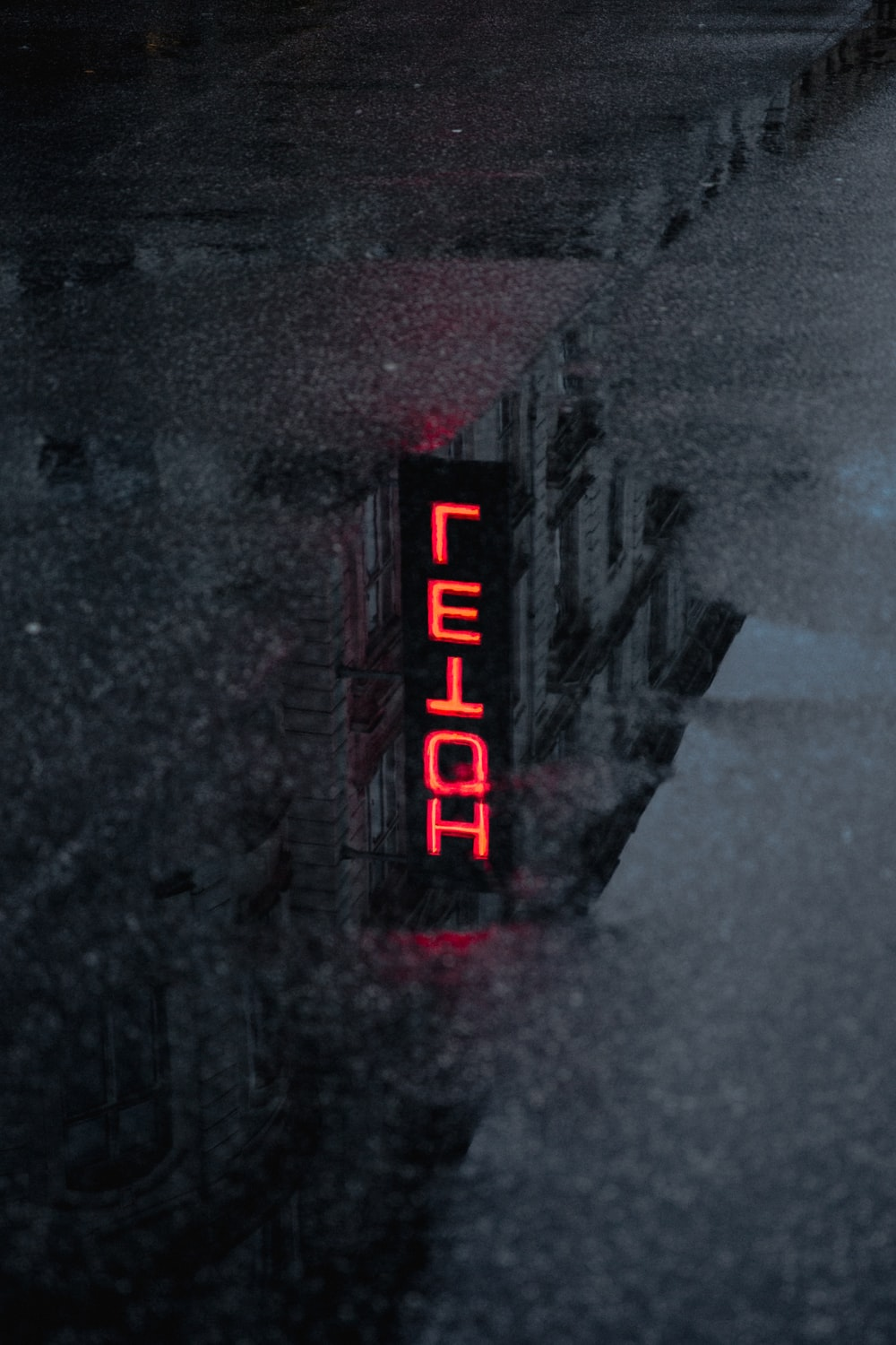 red Hotel neon light signage reflection on puddle during daytime
