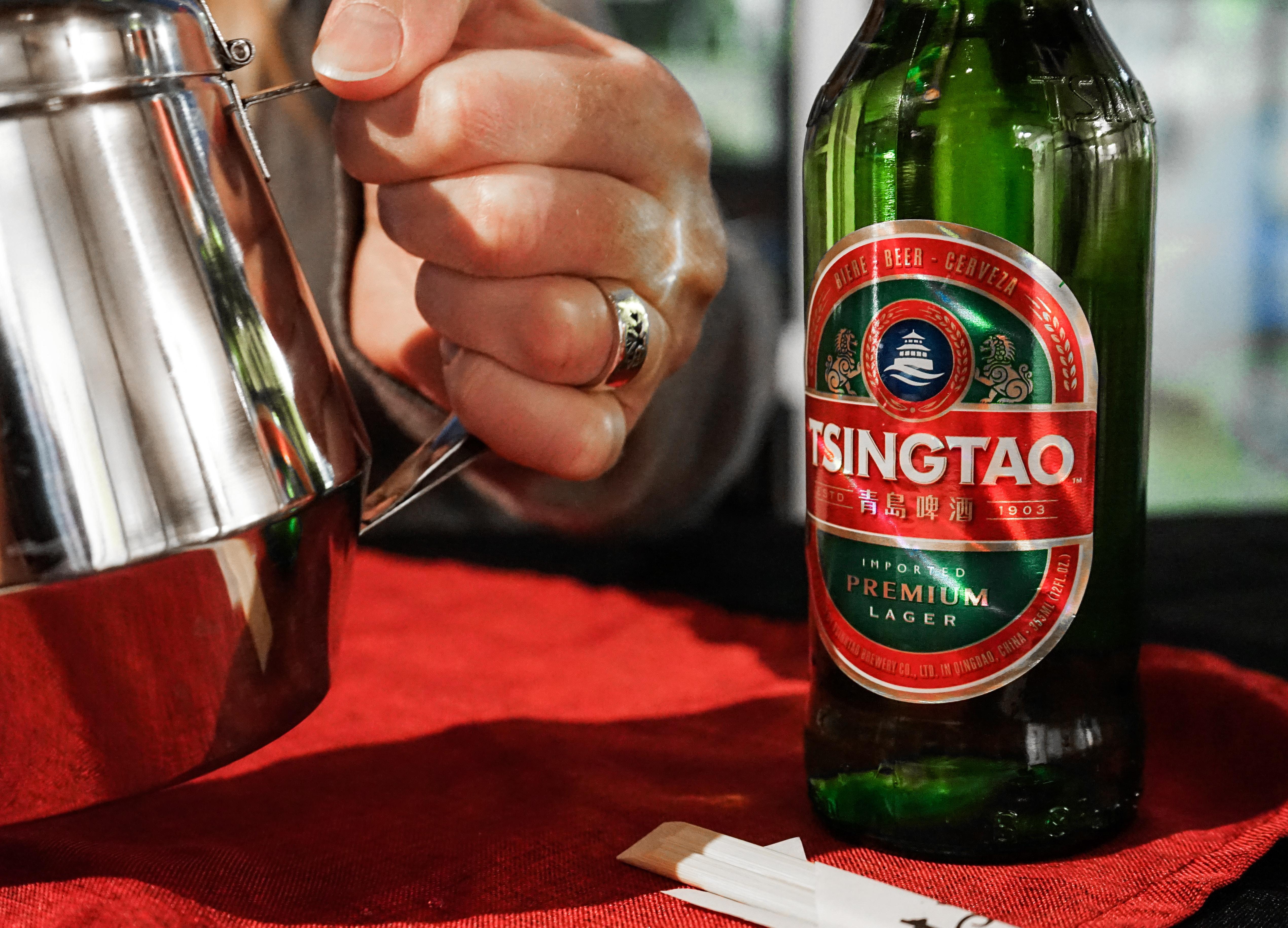 person holding silver pitcher beside a green Tsingtao bottle