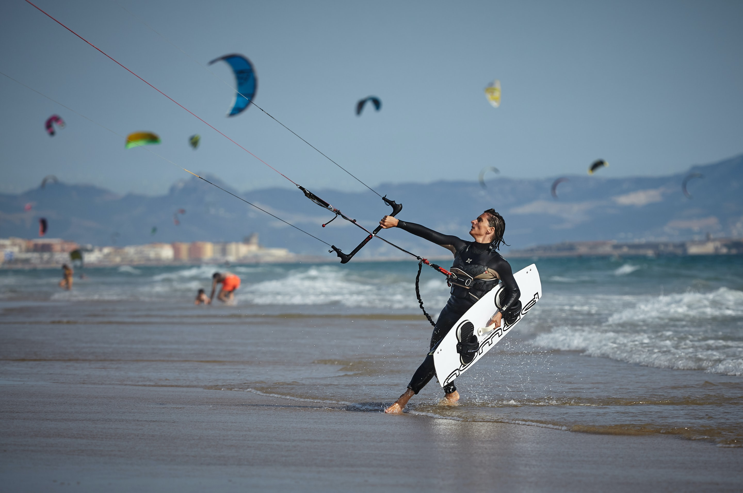 woman holding wakeboard on beach