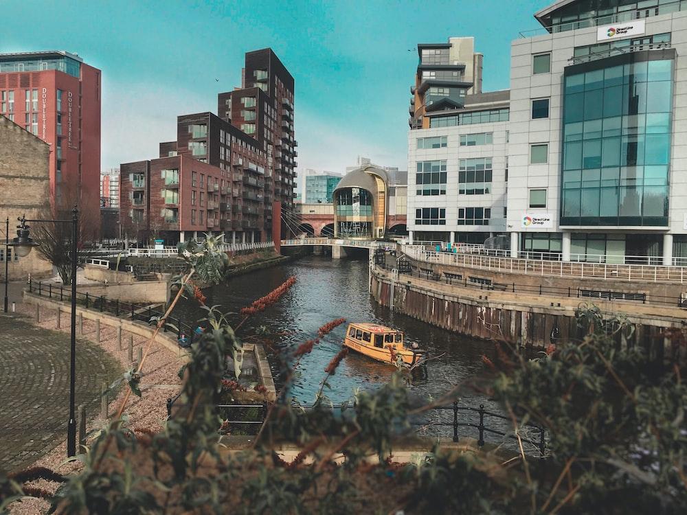 beige boat on body of water between buildings