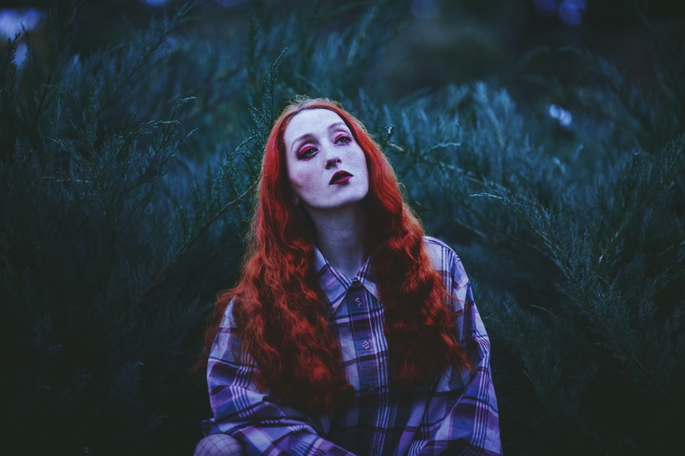 photography of red-haired woman standing near leafed plants