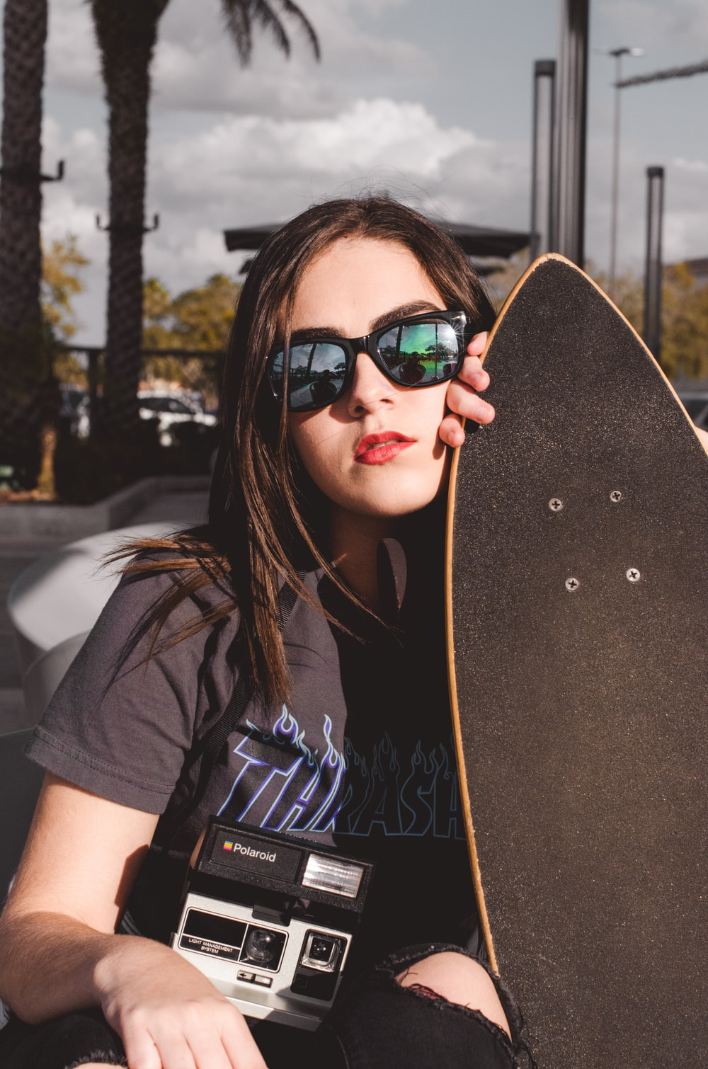 woman holding longboard during daytime