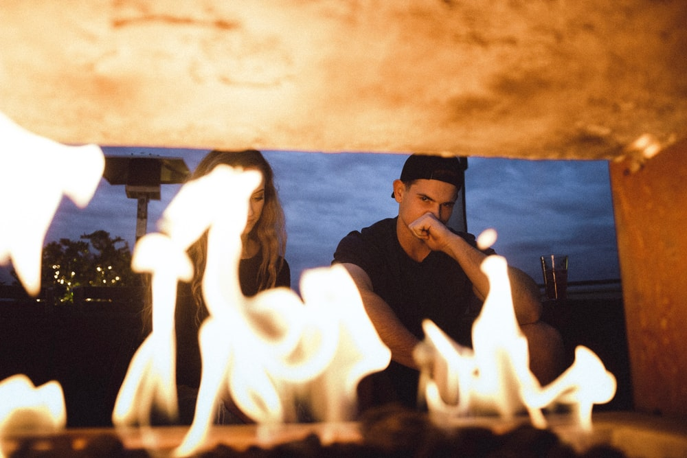 man and woman sitting in front of furnace