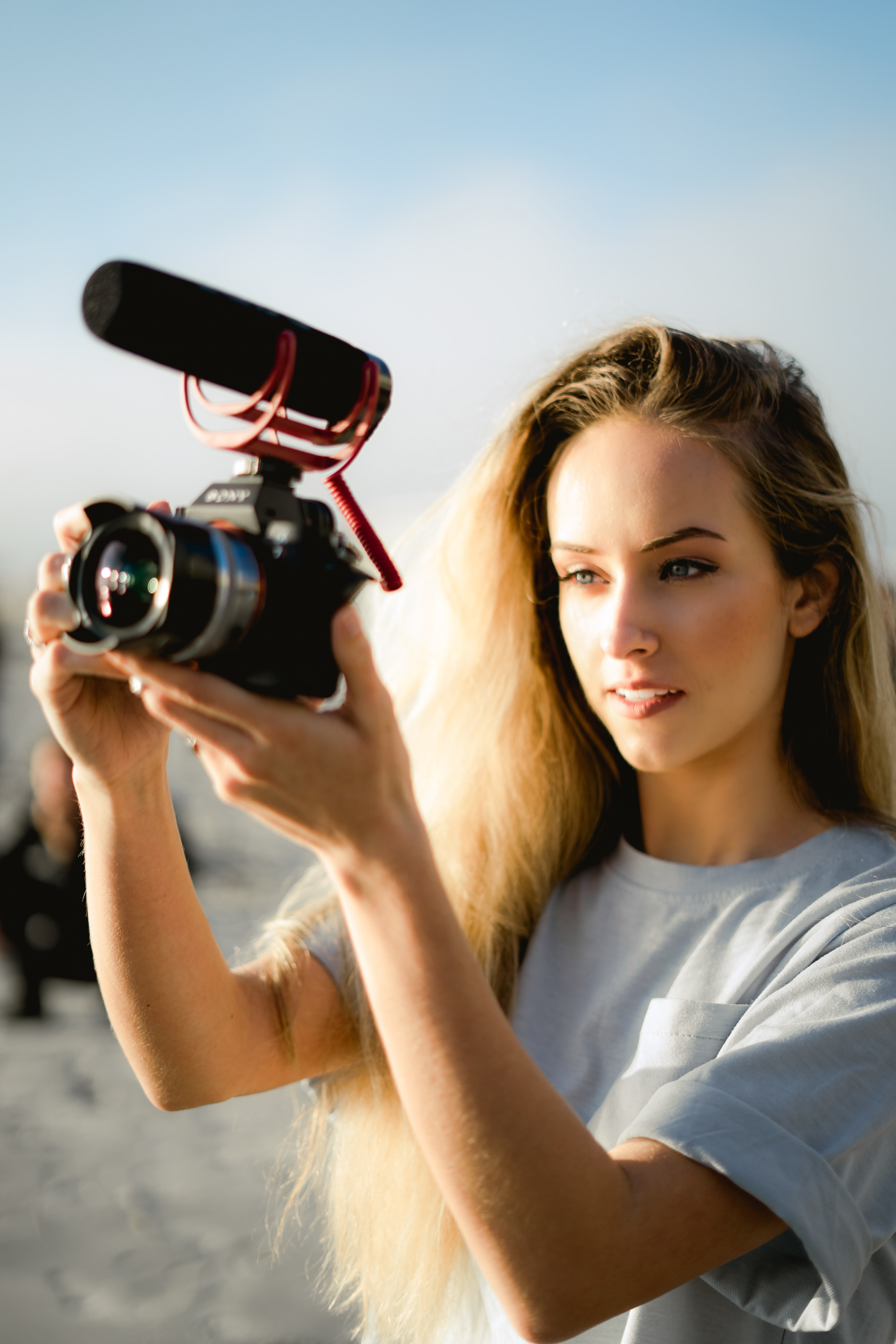 woman holding black DSLR camera with video mic while standing