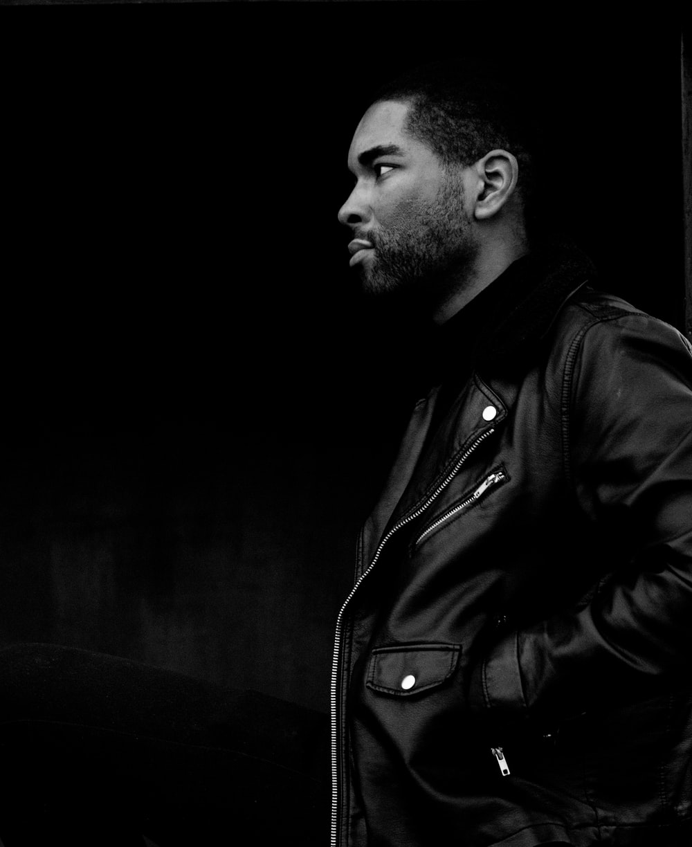 grayscale photography of man wearing leather jacket