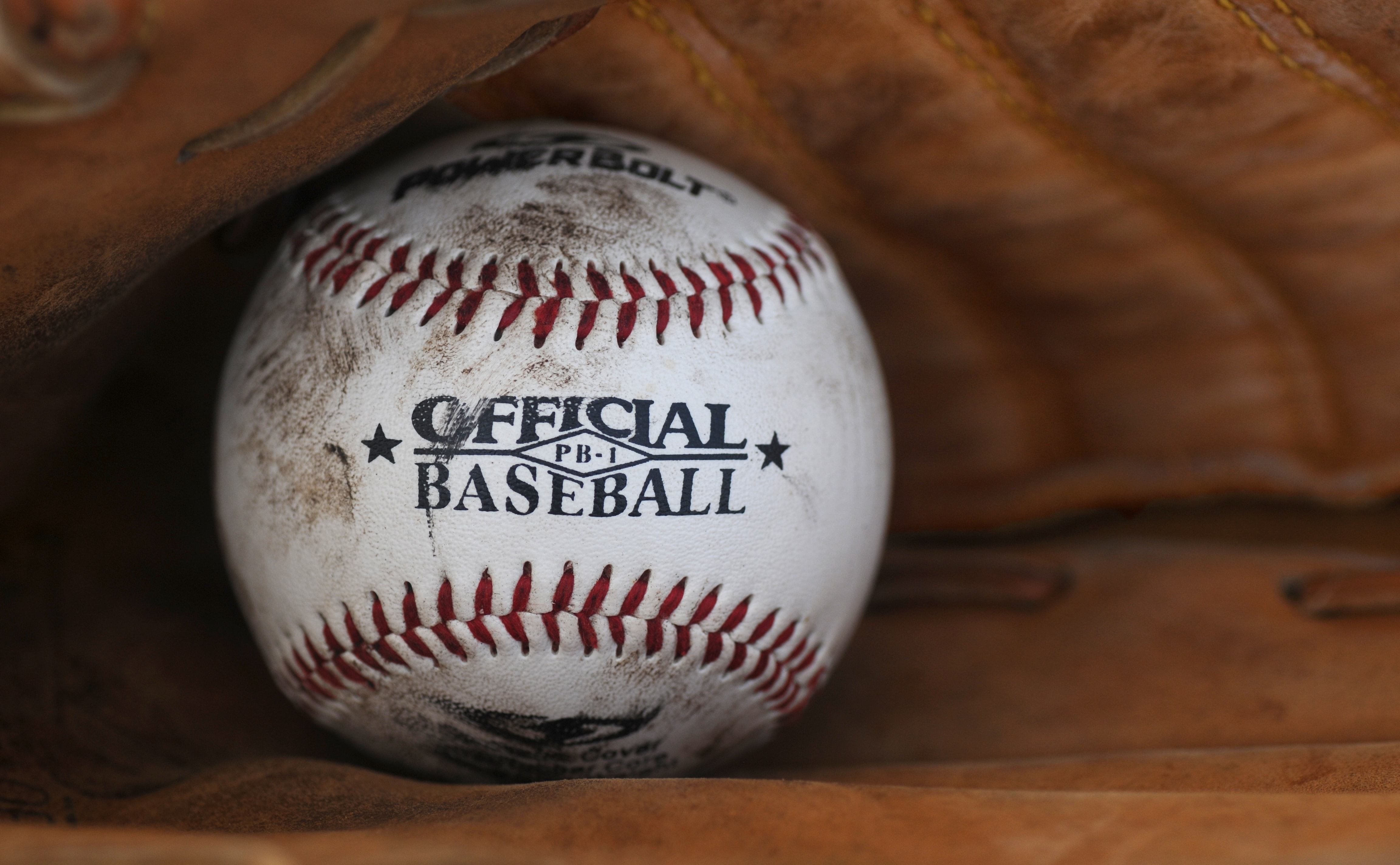 dirt covered Official Baseball ball in person's baseball mitts