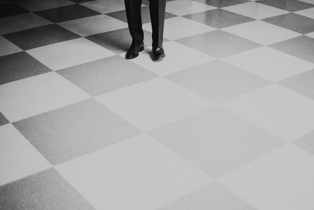 person standing on gray and black checkered floor
