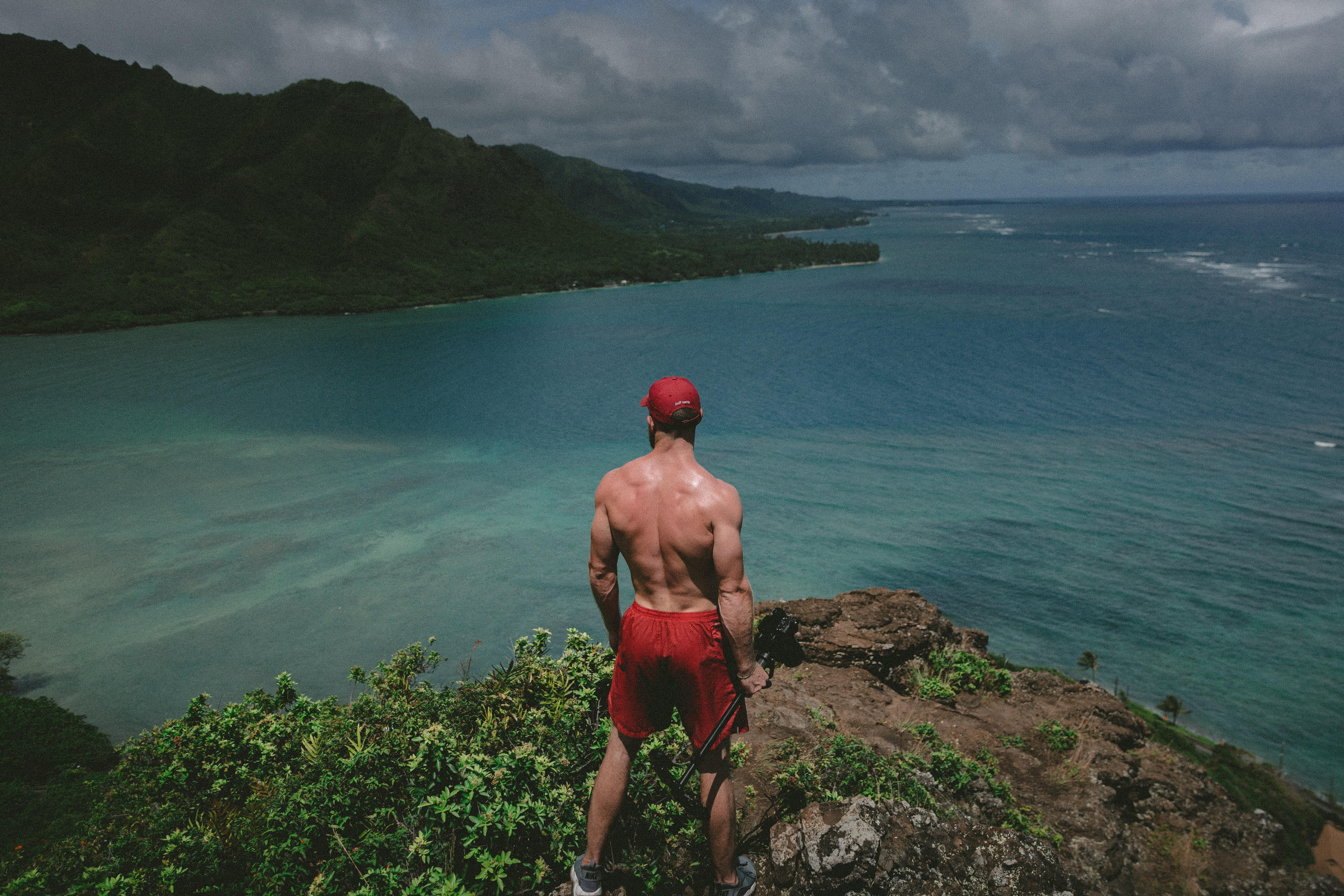 man standing on top of clipp watching body of water during daytime