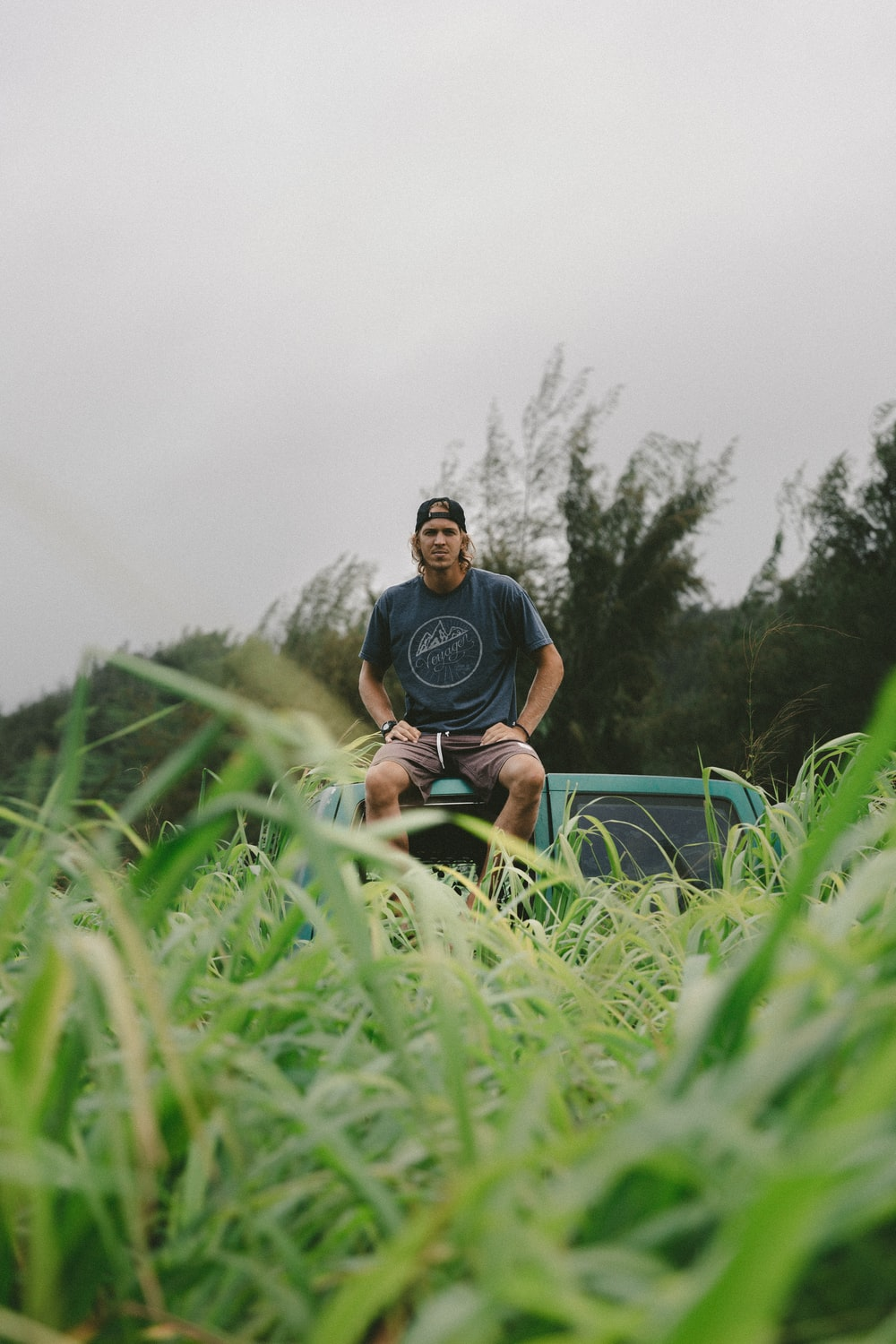 man in black crew-neck t-shirt sitting on green vehicle roof