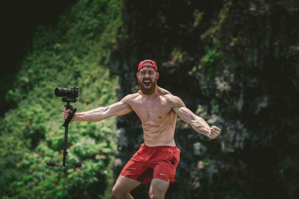standing man wearing red shorts and holding black camera