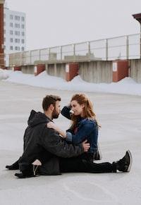 woman sitting on man's lap during daytime