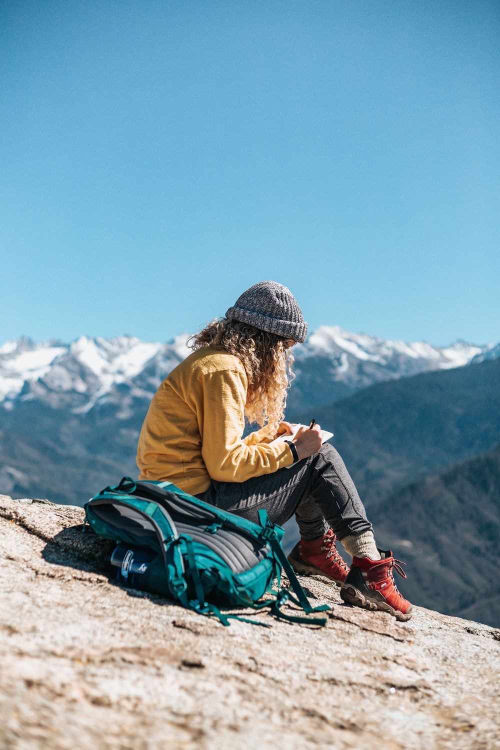 woman writing while sitting on hill near mountain