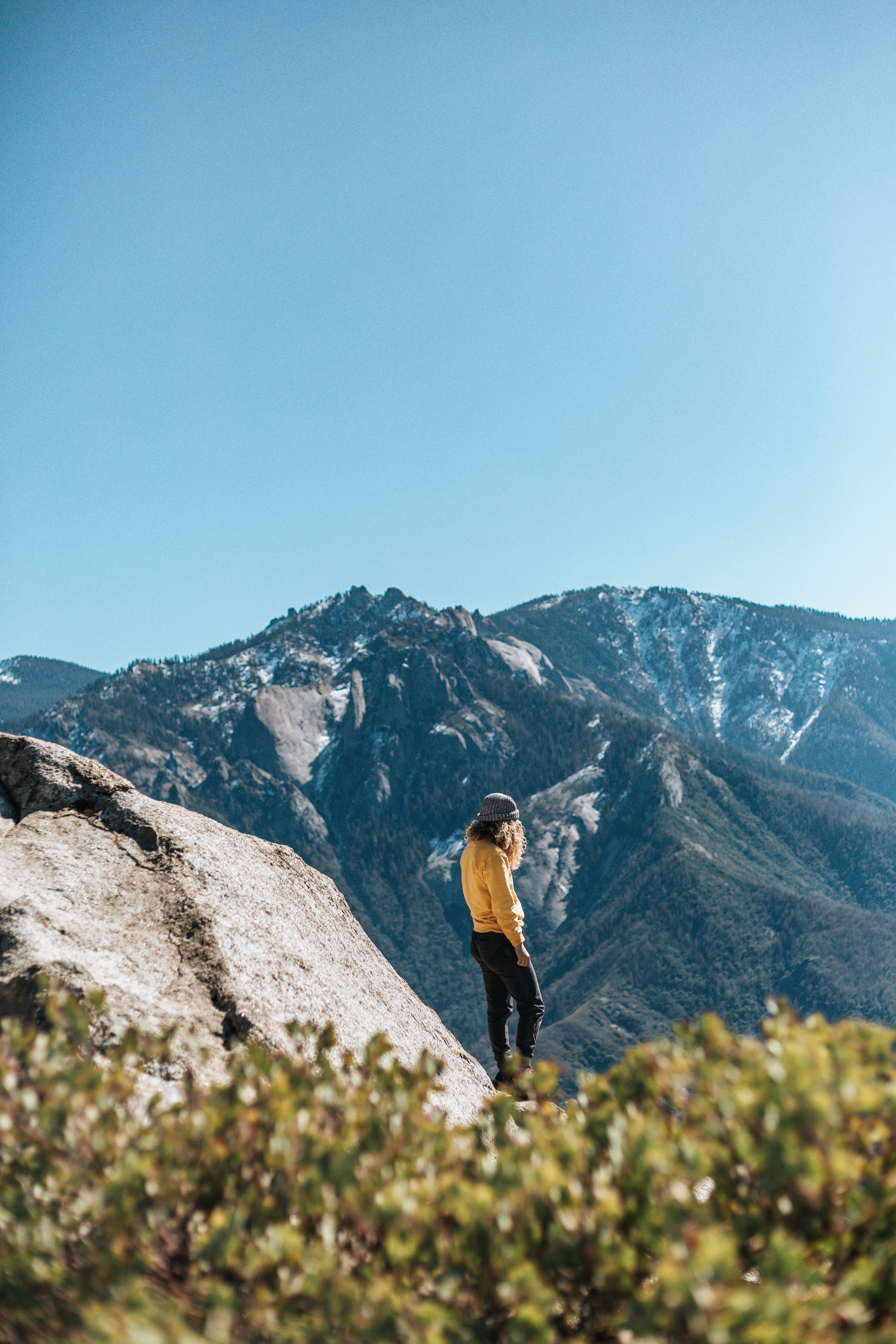 woman in yellow sweatshirt and black pants standing near cliff under blue sky during daytime