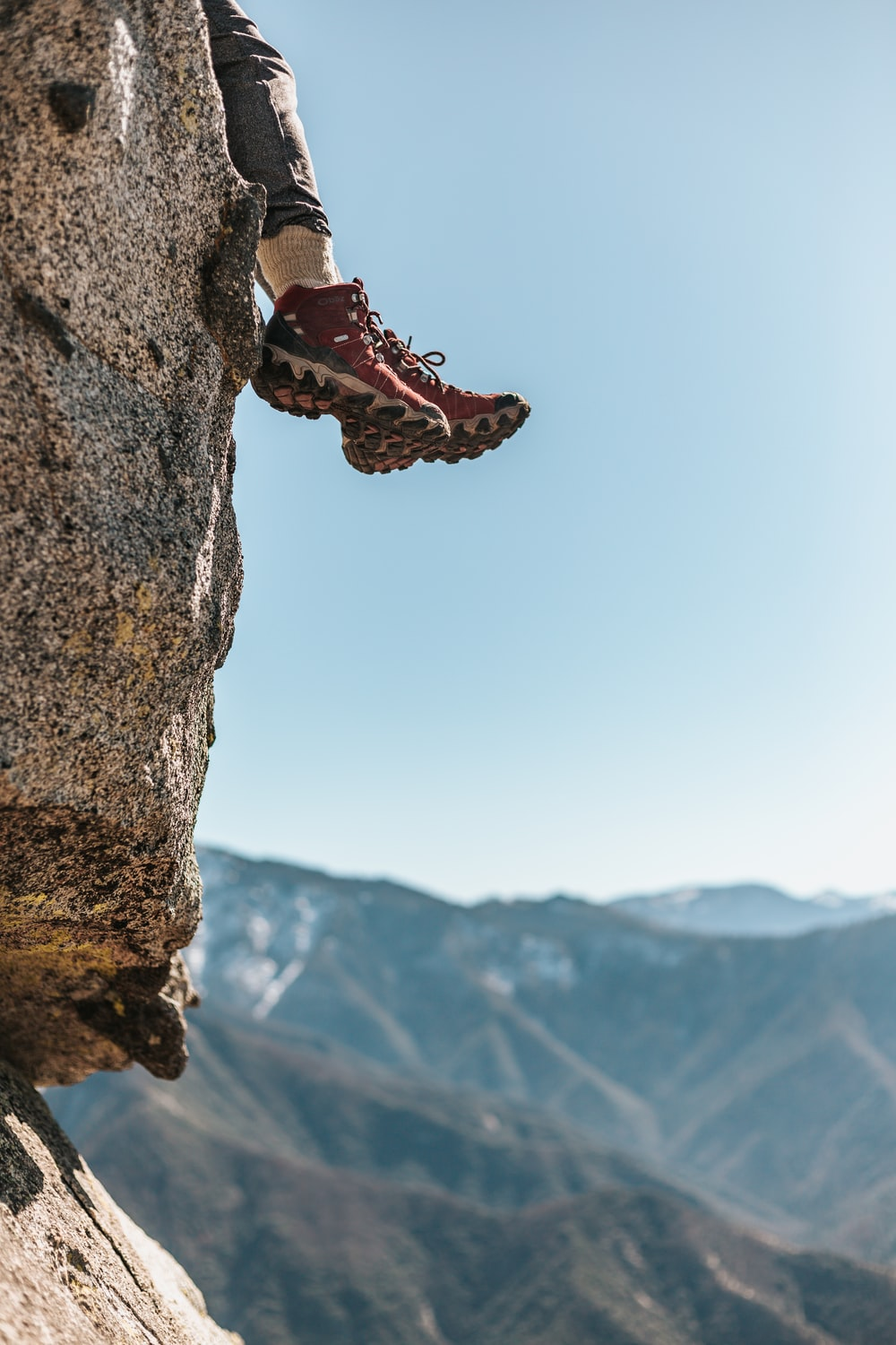 person wearing pair of red-and-white hiking shoes sitting on rocky cliff across mountains during daytime