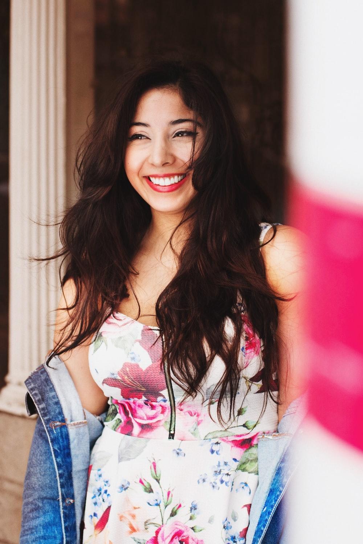 woman wears floral dress smile inside room