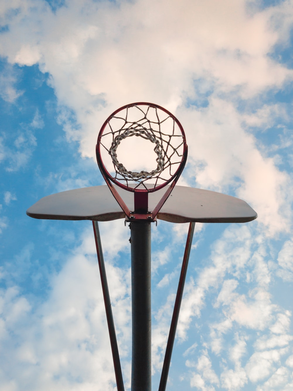 low-angle photo of red and white basketball hoop