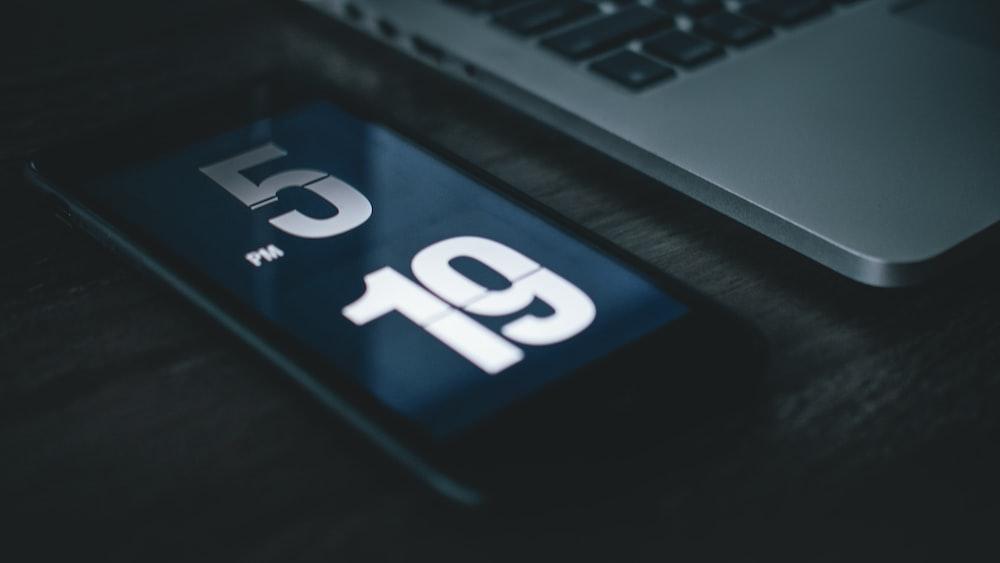 black smartphone beside laptop
