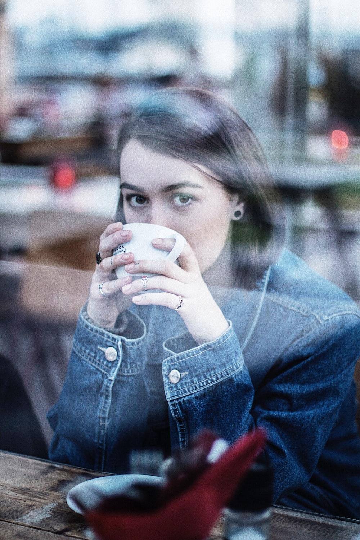 woman wearing blue denim jacket holding white ceramic teacup