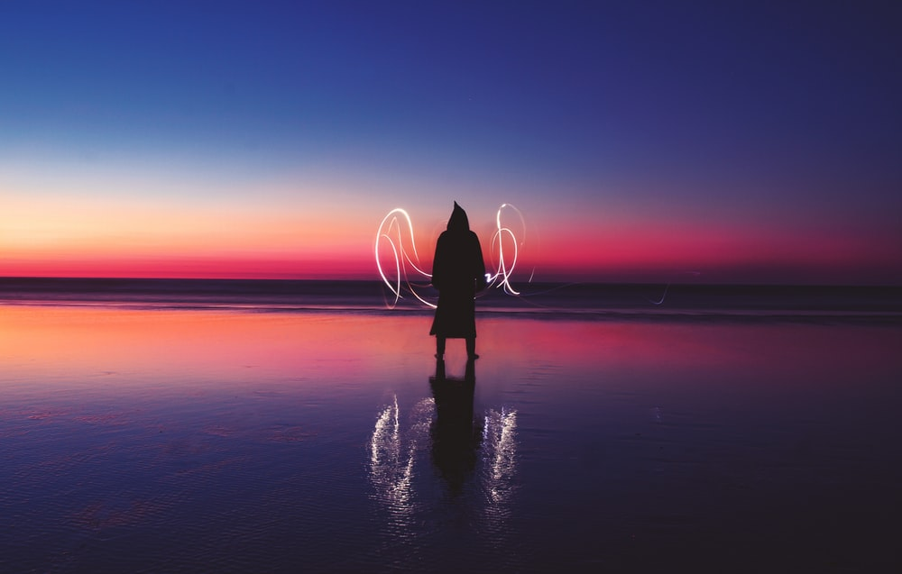 silhouette of person standing on body of water with light wave