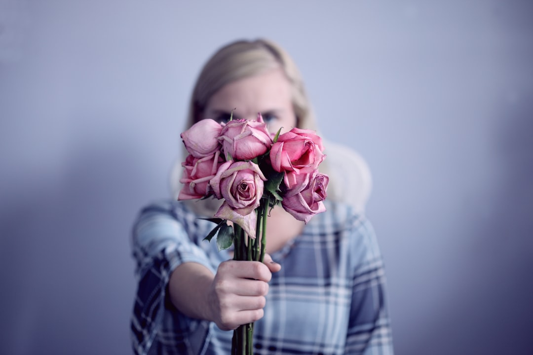 A young woman holding a sad bouquet of dying roses.
