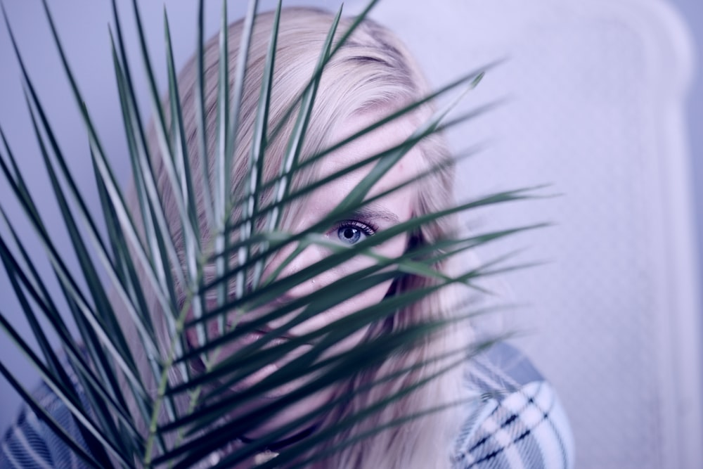 woman covering face with leaves