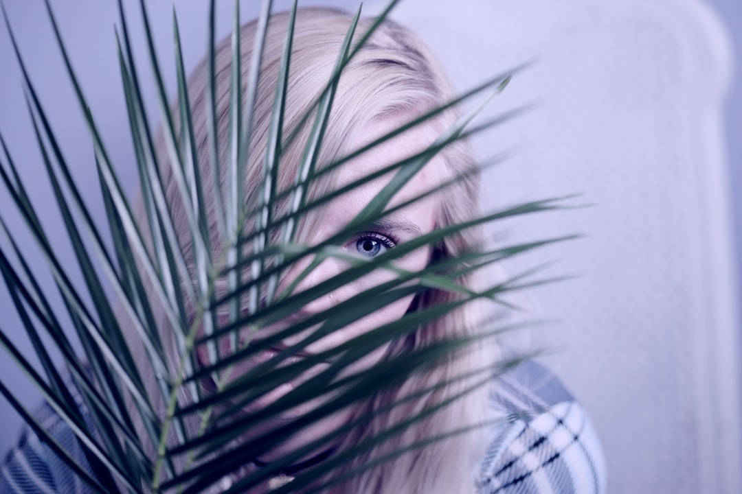 A young woman looking from behind a small palm leaf.
