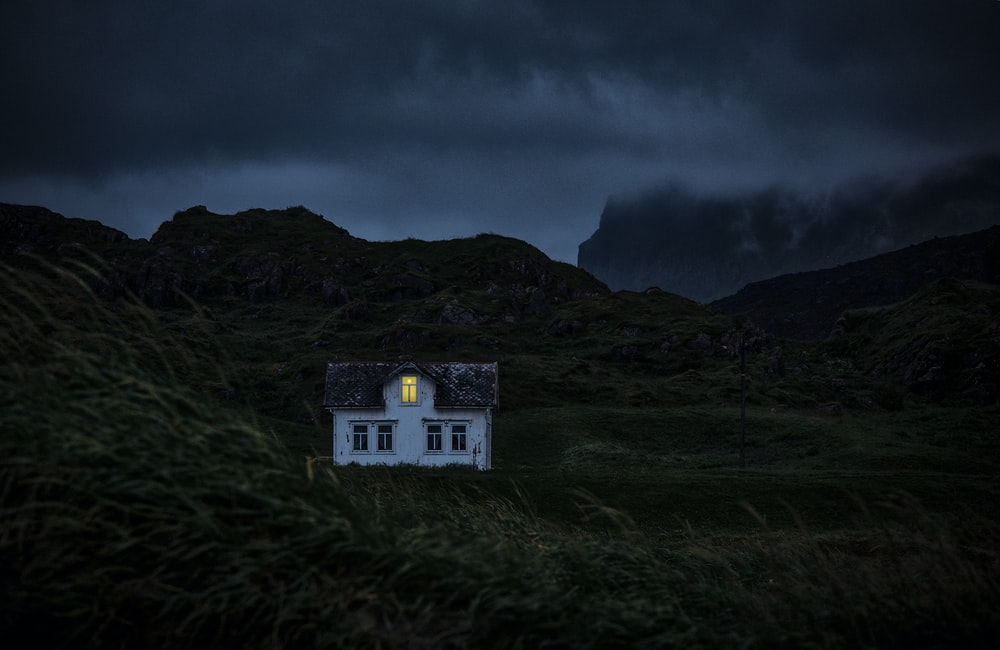white and brown house on mountain under black clouds