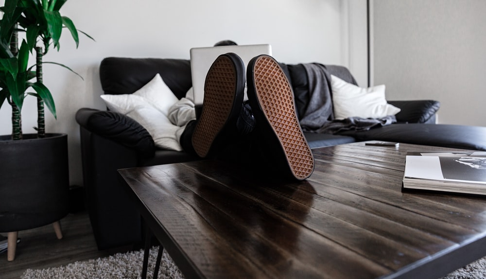 person sitting on sofa resting its feet on top of coffee table while using laptop