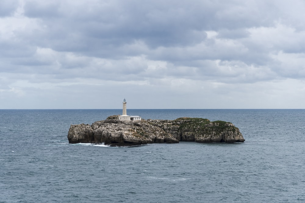 lighthouse on islet under cloudy skies