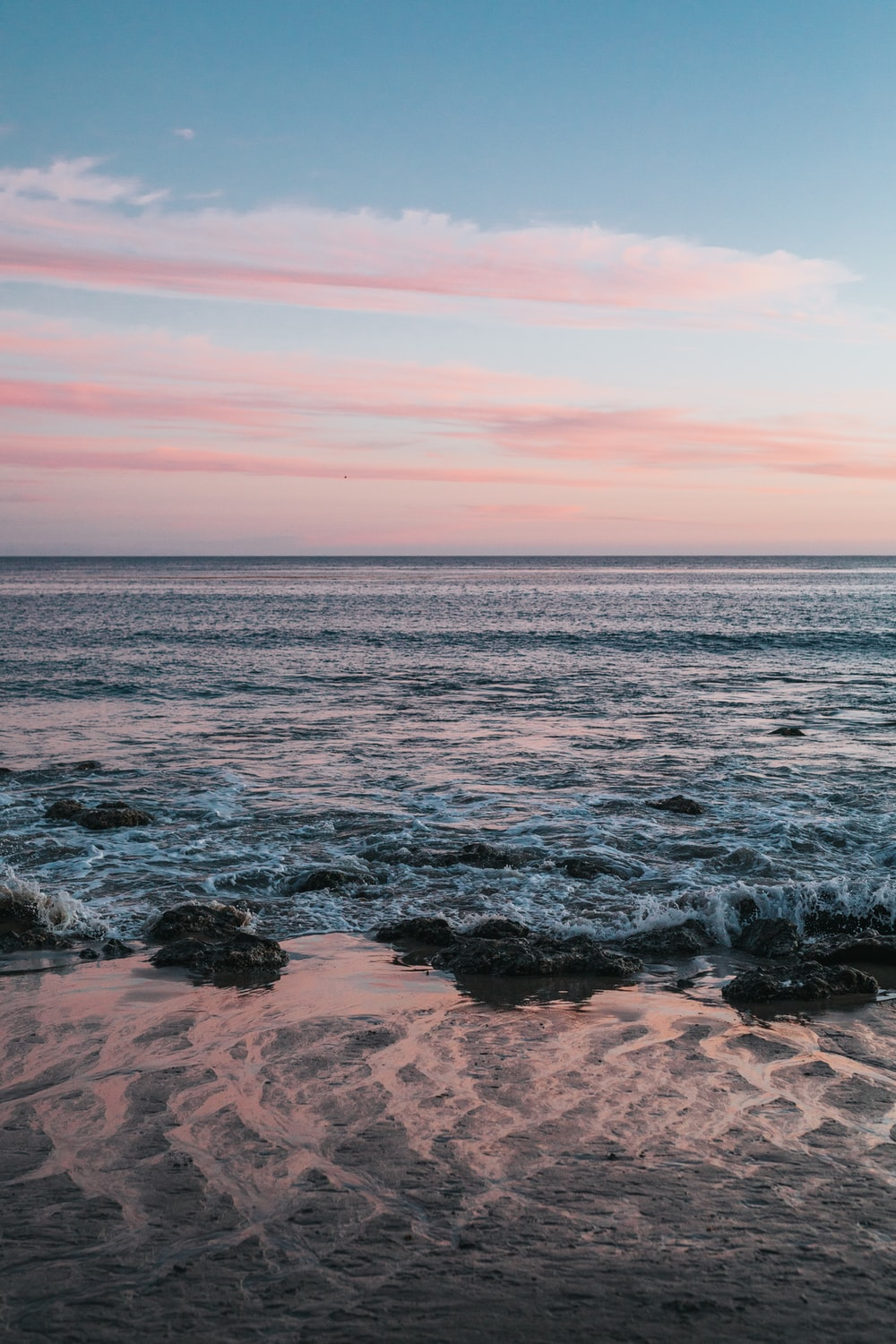 body of water with pink sky