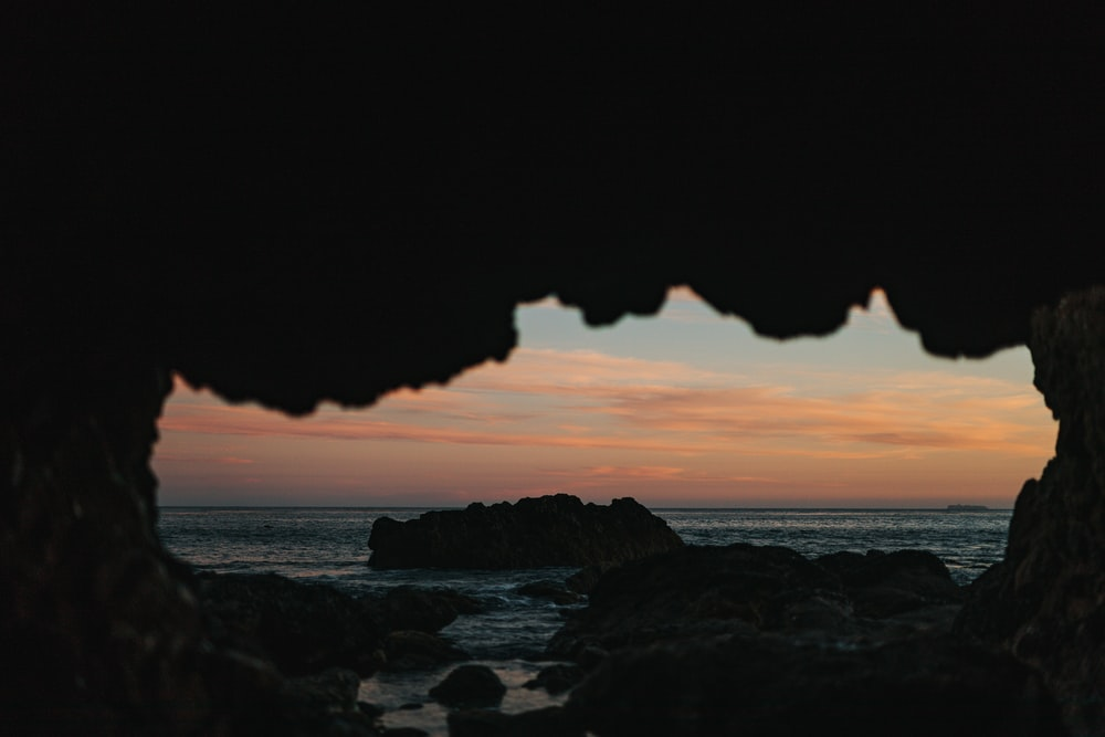 view of ocean from a cave during sunset