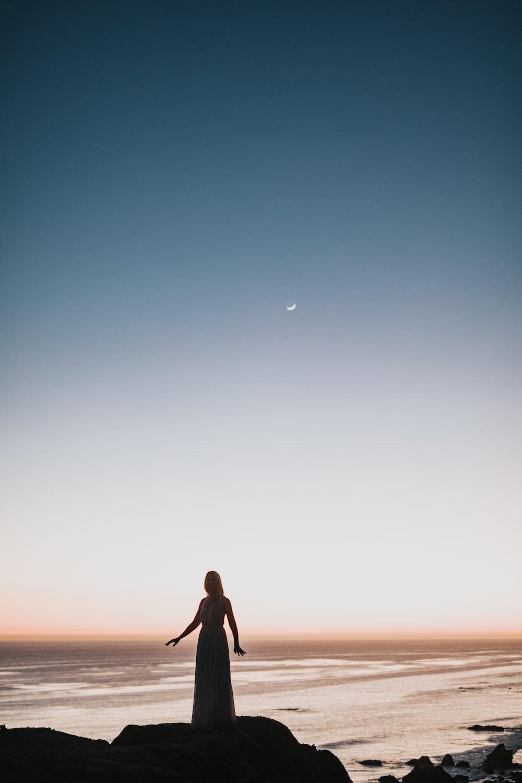 woman in dress standing near body of water