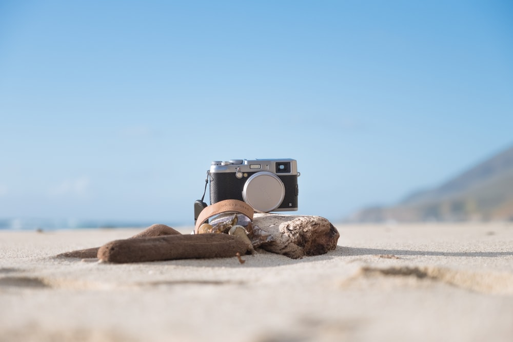 selective focus photography of camera on sand