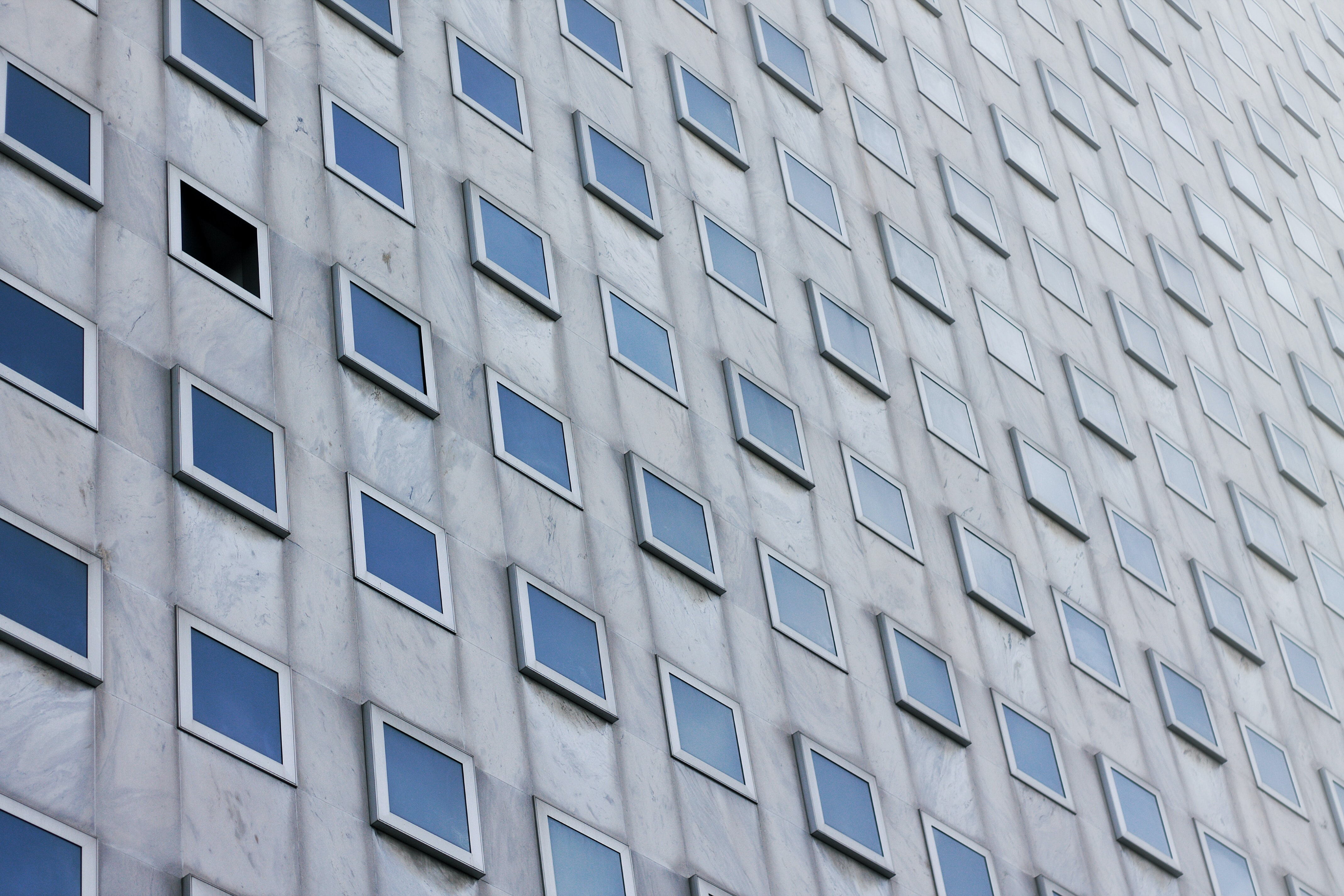 photo of gray concrete building with clear glass windows at daytime