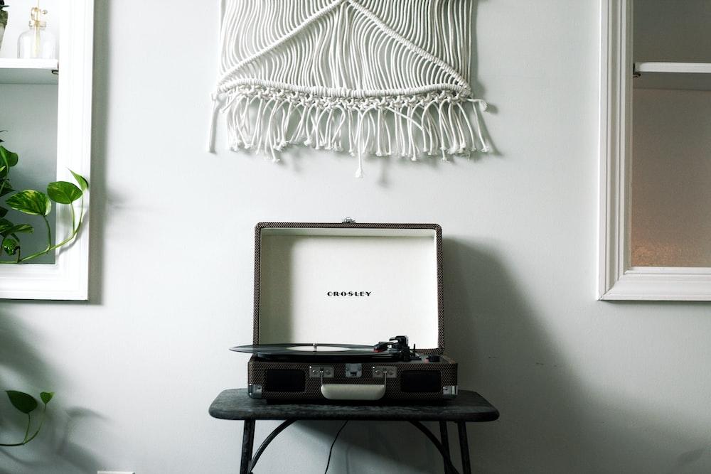 black Crosley turntable on black table near white wall