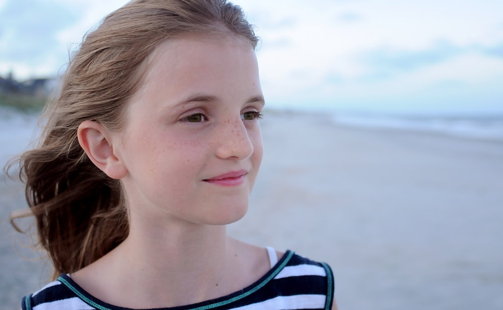 girl standing at beach wearing white, green, and black striped shirt facing left side