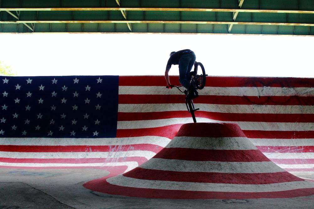 man riding bike performing stunts on ramp during daytime