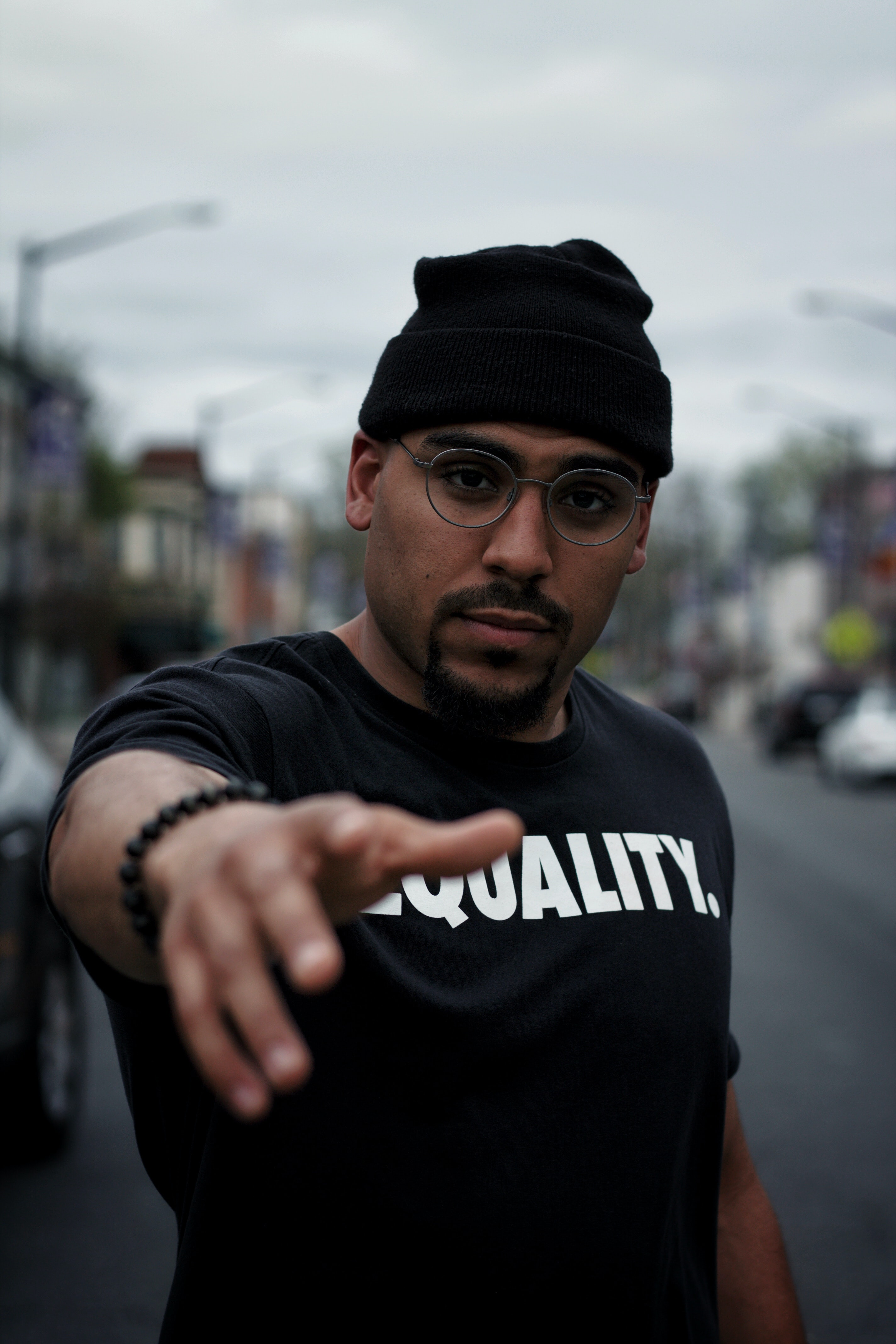 Black man pointing wearing shirt which says equality