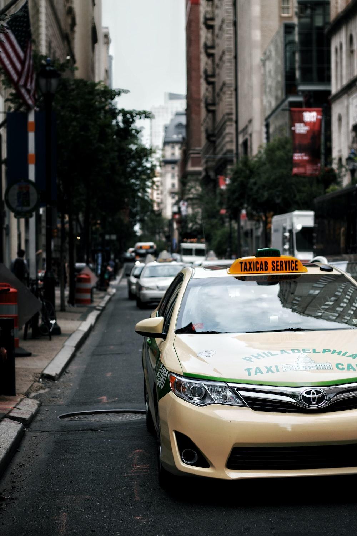 white taxi on gray asphalt road during daytime