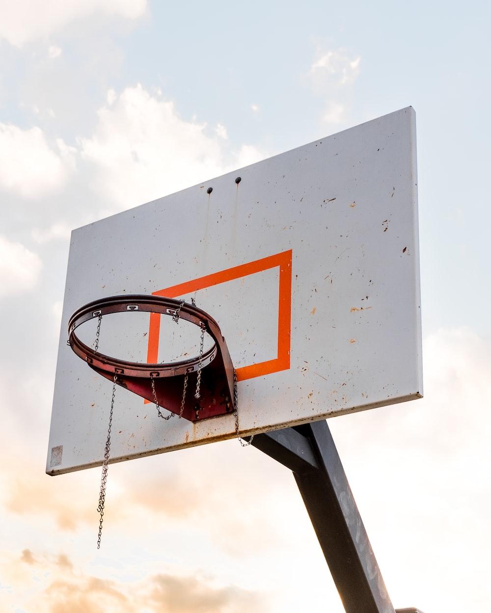 orange steel basketball hoop mounted on white wooden basketball hoop board
