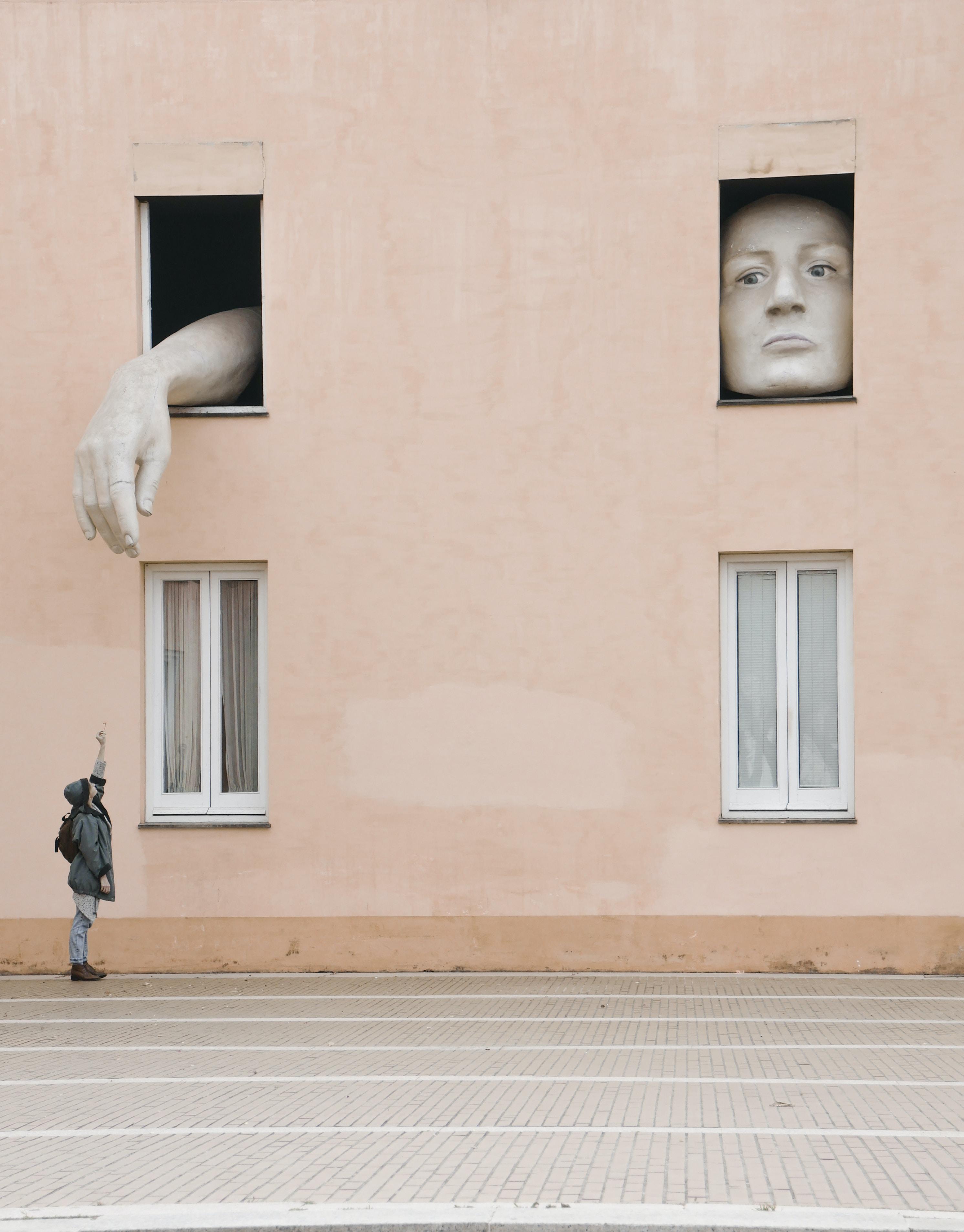 person raising hand under the window
