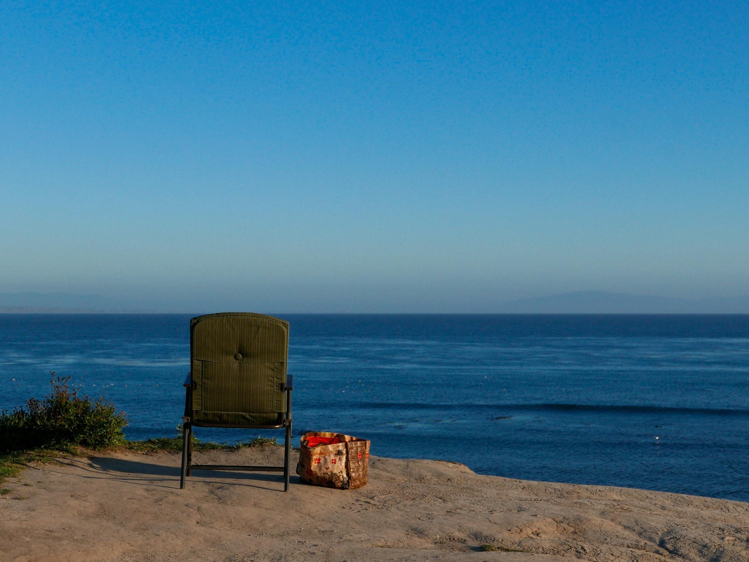 brown armchair near sea shore
