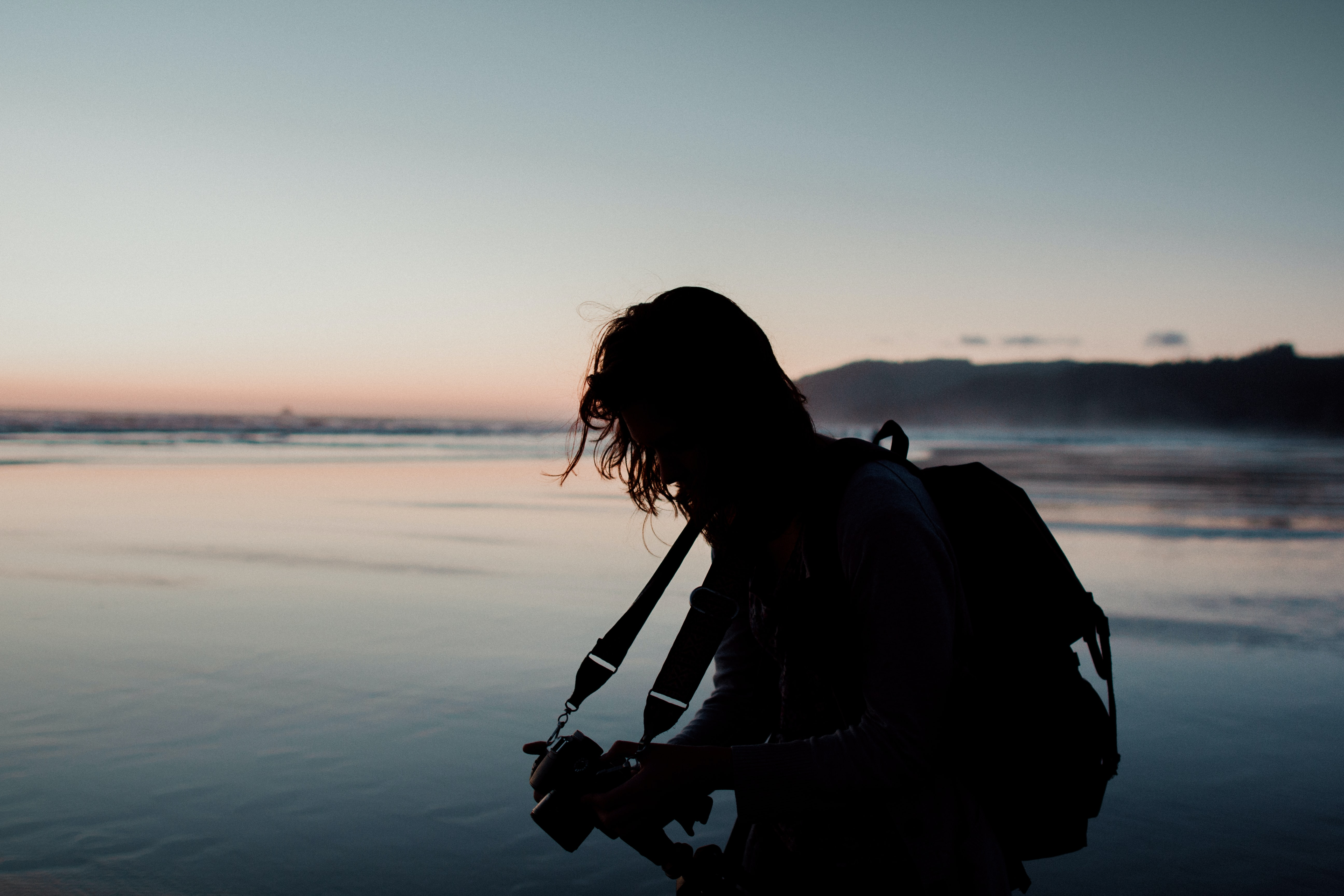 silhouette photo of man holding a camera beside body of water