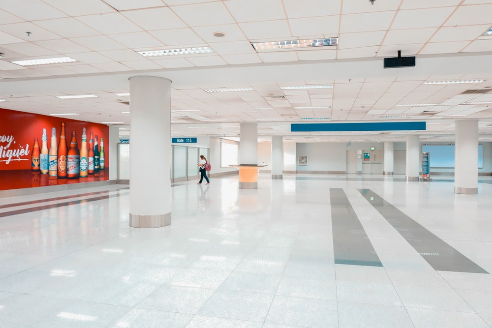 woman walking in white lobby