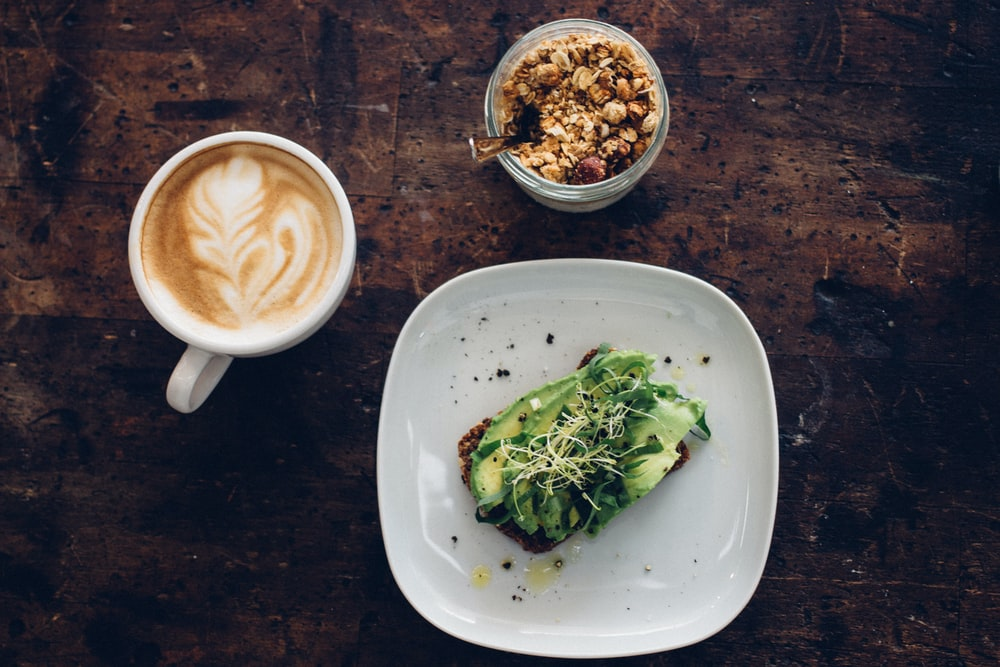 sliced vegetable on plate near coffee cup and nuts on glass container