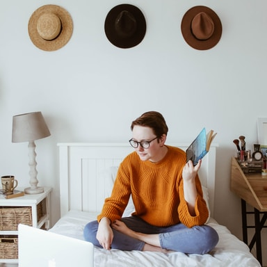 woman sitting on bed facing laptop