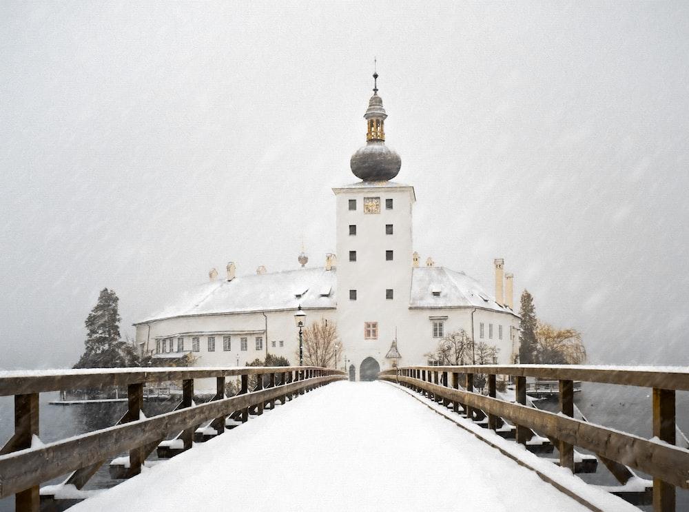 white concrete building near snow covered bridge